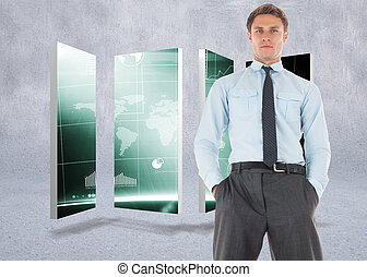 Serious businessman standing with hands in pockets against grey wall