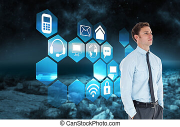 Serious businessman standing with hands in pockets against rocky landscape