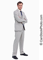 Serious businessman standing with his arms folded