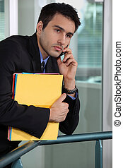 Serious businessman talking on his mobile phone and holding files