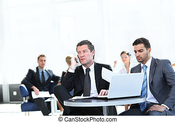 serious businessman talking on mobile phone sitting at your Desk
