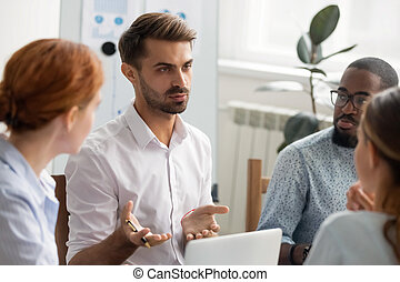 Serious businessman talking with group of business partners at meeting