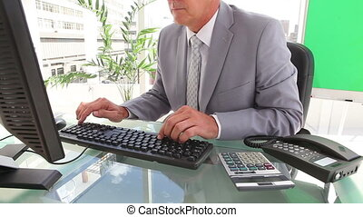 Serious businessman typing before making a call