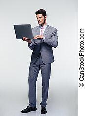Serious businessman using laptop