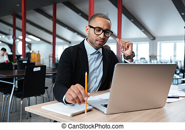 Serious businessman using laptop in the office
