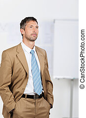 Serious Businessman With Hands In Pockets Standing In Office