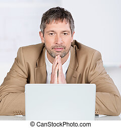 Serious Businessman With Laptop In Office