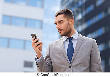 serious businessman with smartphone outdoors - business,...