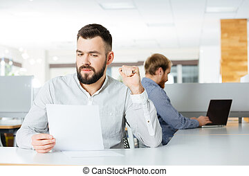 Serious  businessman working with documents in office