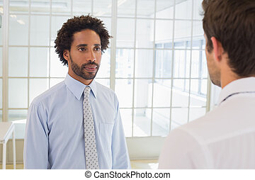 Serious businessmen looking at each other in office
