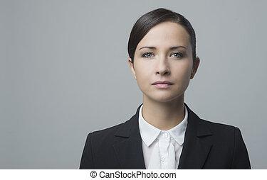 Serious businesswoman against gray background