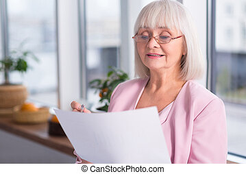 Serious businesswoman examining a document
