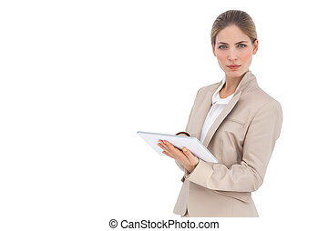 Serious businesswoman holding digital tablet