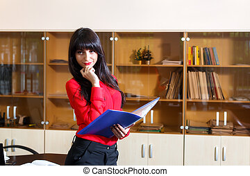 Serious businesswoman in red blouse with a folder of documents in office