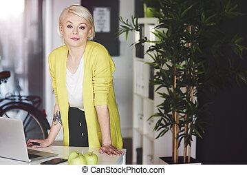 Serious businesswoman leaning on desk
