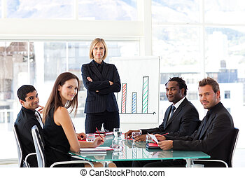 Serious businesswoman looking at the camera with her team