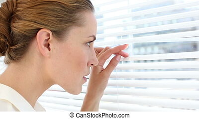 Serious businesswoman peeking through blinds - Serious...