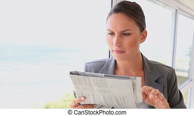 Serious businesswoman reading a newspaper