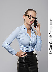 Serious businesswoman talking on mobile phone