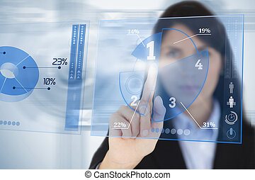 Serious businesswoman using blue pie chart futuristic interface by touching it