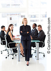 Serious businesswoman with folded arms in a meeting