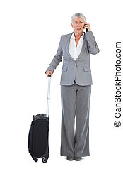 Serious businesswoman with her luggage and calling someone