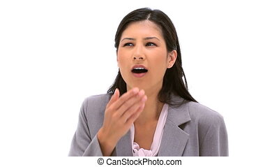 Serious businesswoman yawning against a white background