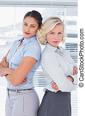 Serious businesswomen with arms folded