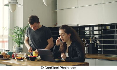 serious caucasian nice couple in kitchen, man is cutting salad, he is standing silent, woman is sitting at table working on laptop and talking on phone
