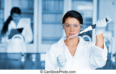 Serious chemist working with large pipette and test tube in...