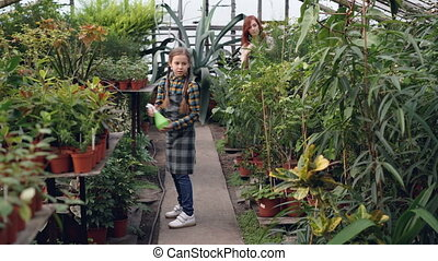 Serious child in apron is watering flowers using spray bottle while her young mother is working in greenhouse. Family business, interesting hobby and people concept.