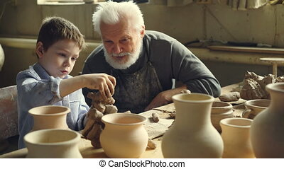 Serious child is kneading clay and talking to his...