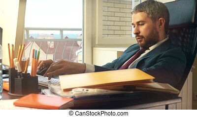 Serious confident businessman working on his computer at the...