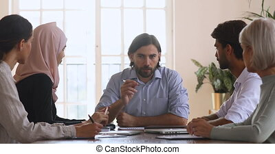 Serious confident young bearded businessman team leader holding daily meeting.