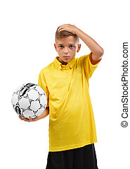 Serious, confused boy with a soccer ball holding his head isolated on a white background. School activities concept.