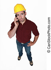 Serious construction worker on the phone