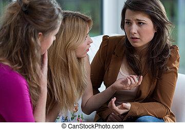 Three pretty friends having a serious conversation