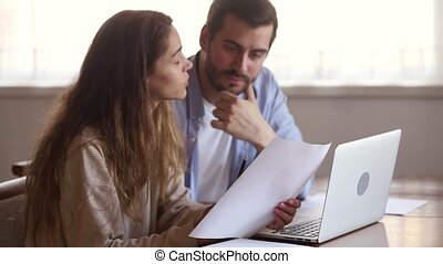 Serious couple holding papers reading domestic bills sitting with laptop