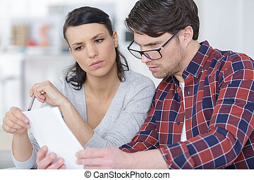 serious couple looking at paperwork together