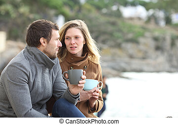 Serious couple of adults talking in winter on the beach