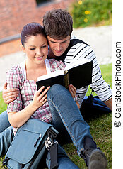 Serious couple of students reading a book sitting on grass