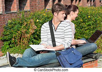 Serious couple of students working together with book and laptop in the campus of their university