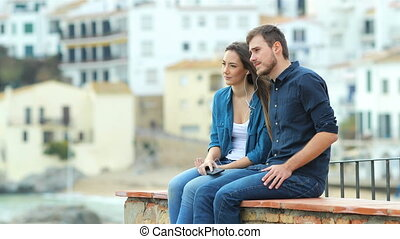 Serious couple sharing music and breathing outdoors sitting...