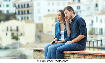 Serious couple sharing music from a smart phone outdoors...