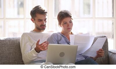 Serious couple talking having problem with paying bills on laptop