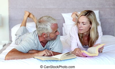 Serious couple talking together in the bed while holding books