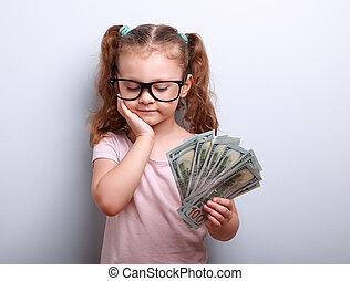 Serious cute kid in glasses looking on dollars in hand and ...