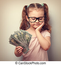 Serious cute kid in glasses looking on dollars in hand and thinking how to spend money. Vintage portrait