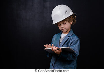 Serious cute little boy in hardhat and formalwear using digital tablet