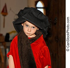 Serious cute little boy in medieval costume standing